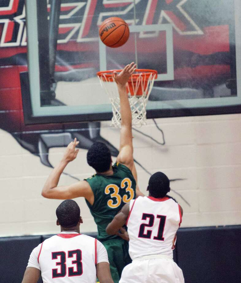 Cy-Falls' Kavin Tilbury (33) score the winning basket with a shot over Langham Creek's Eric Thomas (21) during a District 17-5A basketball game between Cy-Falls and Langham Creek, Friday, February 1, 2013. Cy-Falls wins in overtime. (Bob Levey/For The Chronicle) Photo: Bob Levey, Houston Chronicle / ©2013 Bob Levey