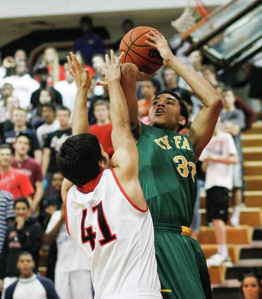 Cy-Falls' Kavin Tilbury (33) shoots over Langham Creek's Eric Johnson (41) during a District 17-5A b