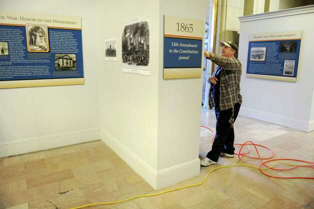 Joe Wills, OGS maintenance worker, hangs the Black History Month exhibit on Friday, Feb. 1, 2013, at the Capitol in Albany, N.Y. The exhibit, on display through the month of February, is located on the second floor in the East Gallery. (Cindy Schultz / Times Union) Photo: Cindy Schultz / 10021011A