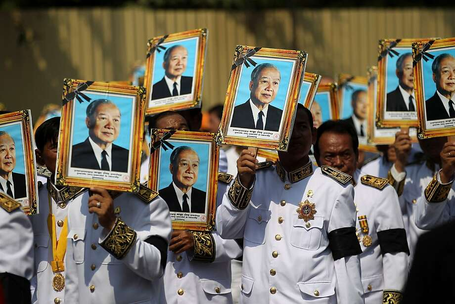 Procession participants shield themselves from the sun with portraits of the late former Cambodian King Norodom Sihanouk in a funeral procession in Phnom Penh, Friday, Feb. 1, 2013. Thousands of mourners accompanied the gilded chariot carrying the body of former King Sihanouk - the dominant figure of modern Cambodia - in the funeral procession Friday to a cremation ground next to the palace where he was crowned more than 70 years ago.  Photo: Wong Maye-E, Associated Press