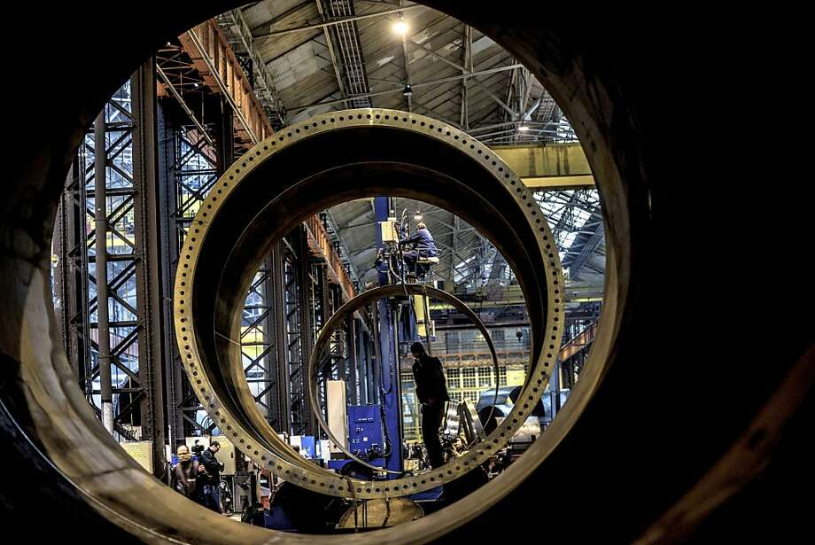 Employees assemble pieces of a mast of a wind turbine on February 1, 2013 the FrancEole wind turbines factory in Le Creusot. Photo: Jeff Pachoud, AFP/Getty Images