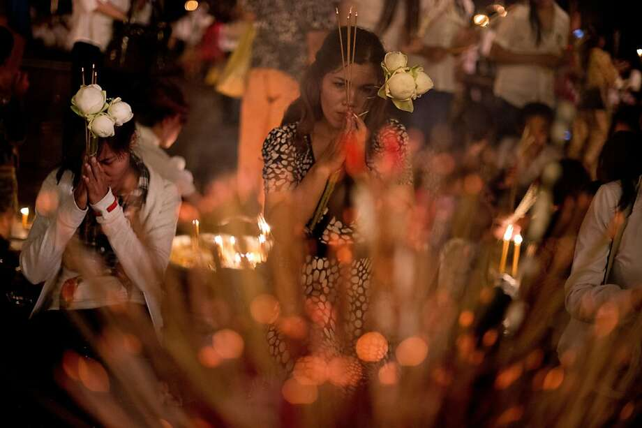 Cambodians pray and burn incense sticks as they pay respects for the late former King Norodom Sihanouk in front of the Royal Palace in Phnom Penh on February 1, 2013. Sihanouk, who abdicated in 2004 after steering Cambodia through six decades marked by independence from France, civil war, the murderous Khmer Rouge regime and finally peace, died of a heart attack in Beijing on October 15, 2012 and will be cremated on February 4.  Photo: Nicolas Asfouri, AFP/Getty Images