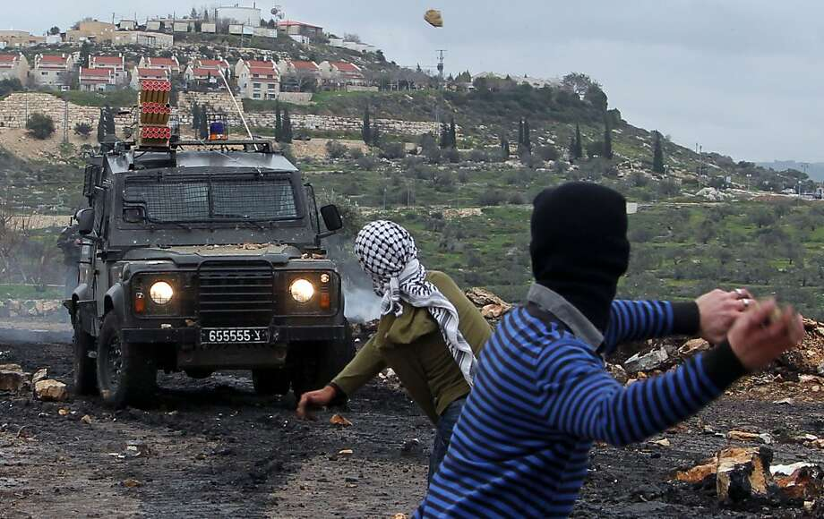 Palestinian protesters rethrow stones at israeli soldiers during clashes following a protest against the expropriation of Palestinian land by Israel on February 1, 2013 in the village of Kafr Qaddum, near Nablus, in the occupied West Bank.  Photo: Jaafar Ashtiyeh, AFP/Getty Images