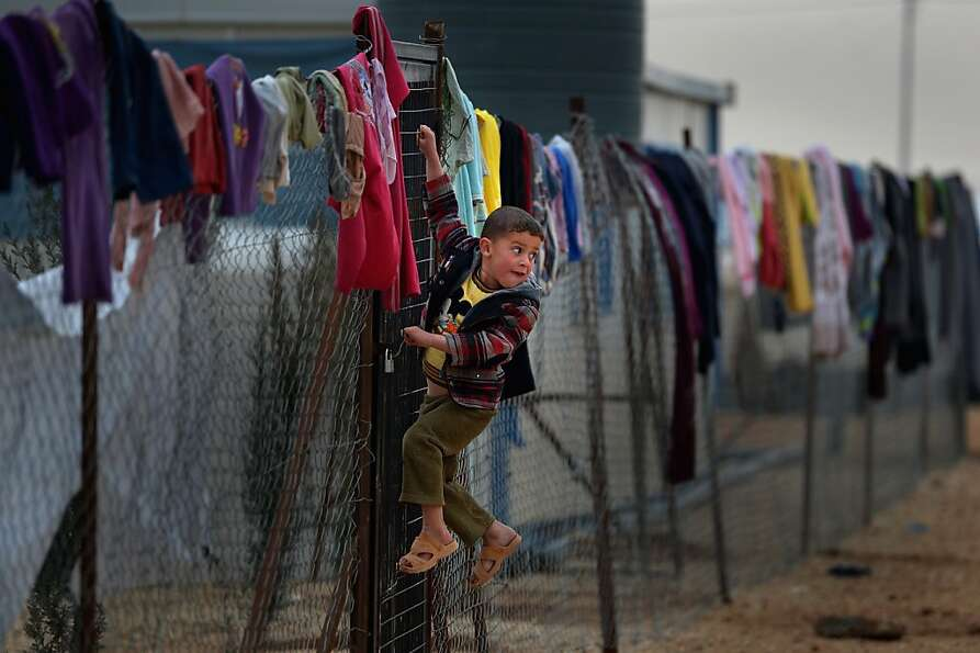 Young boy hangs on a fence with clothing hung from it, as Syrian refugees go about their daily bus