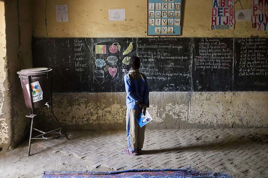 A Malian child stands in front of the black board of his school on February 1, 2013 in Timbuktu, ind