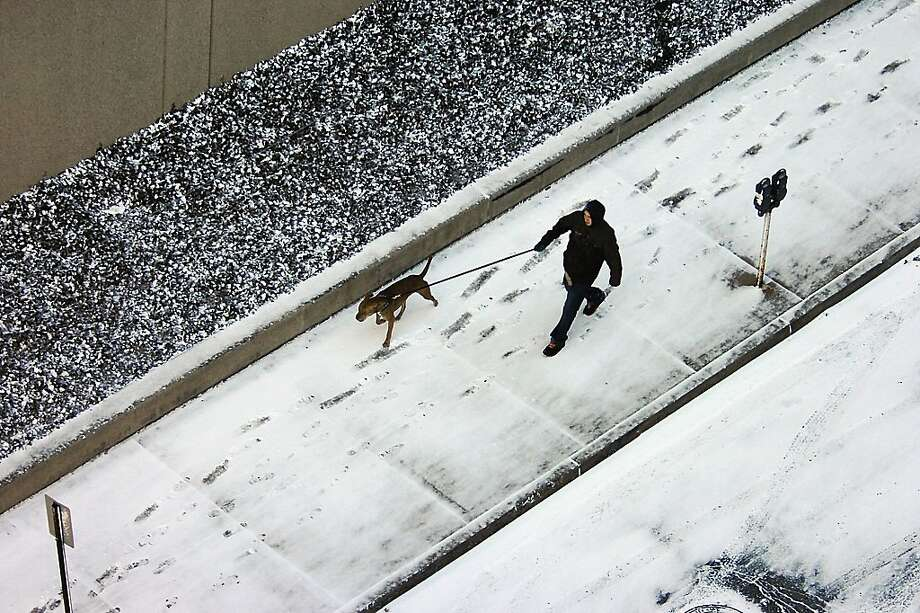 A pedestrian and a dog take a cold walk in between snow squalls on Spruce Street in downtown Scranton, Pa. on Friday, Feb.1, 2013. Photo: Butch Comegys, Associated Press