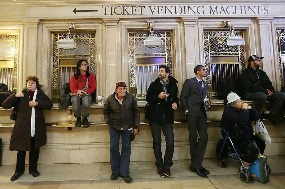 People stand near closed ticket windows in Grand Central Terminal during centennial celebrations on the day the famed Manhattan transit hub turns 100 years old on February 1, 2013 in New York City. The terminal opened in 1913 and is the world's largest terminal covering 49 acres with 33 miles of track. Each day 700,000 people pass through the terminal where Metro-Noth Railroad operates 700 trains per day. Photo: Mario Tama, Getty Images