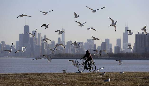 A woman rides her bicycle during a cold day in Chicago, Friday, Feb.1, 2013.  A February hasn't opened this cold here in the 17 years since 1996. The combination of bitterly cold temperatures, hovering at daybreak Friday near or below zero in many corners of the metro area, plus the biting west winds gusting as high as 30 mph, are producing 15 to 25-below zero wind chills, readings as challenging as any Chicagoans have encountered this season.  Photo: Nam Y. Huh, Associated Press
