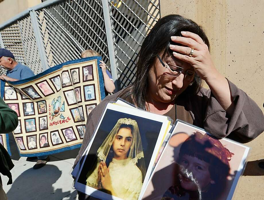 Esther Millar, 54, is overcome with emotion as she talks about her abuser, while holding pictures of Vicki and Mary, who she says were victims of sexual abuse by priest in the Catholic Archdiocese of Los Angeles, during a news conference urging those with information about alleged abuse to come forward on February 1, 2013 at Cathedral of Our Lady of the Angels in Los Angeles, California. Retired Cardinal Roger Mahony of Catholic Archdiocese of Los Angeles, who avoided criminal charges over the way he handled pedophile priests during his career, was reportedly stripped of his archdiocese duties February 1, by his successor Archbishop Jose Gomez. Photo: Kevork Djansezian, Getty Images