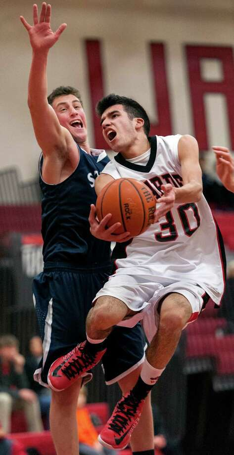 Fairfield Warde high school's Nicholas Cotto goes up for a shot as Staples high school's Todd Goldstein tries to block his shot in a boys basketball game played at Fairfield Warde high school, Fairfield, CT on Friday February 1st, 2013. Photo: Mark Conrad / Connecticut Post Freelance