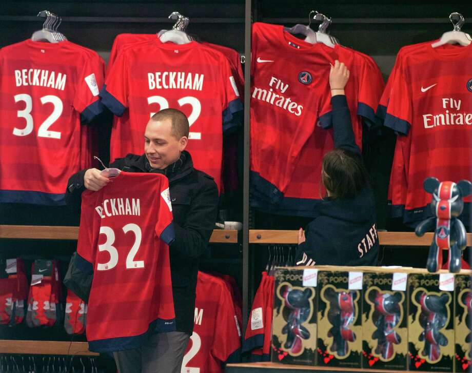 A man looks at a soccer shirt on display with the name of British soccer player David Beckham, at the the Club's shop on the Champs Elysees, in Paris, Friday, Feb. 1, 2013. The jersey is on sale for euros 110 ($150).  David Beckham lit up a subdued transfer deadline day in Europe by securing perhaps the final move of his globetrotting career, a surprise short-term deal with ambitious French club Paris Saint-Germain. (AP Photo/Michel Euler) Photo: Michel Euler