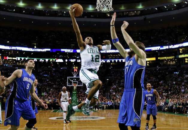 Boston Celtics guard Leandro Barbosa (12) drives to the basket against Orlando Magic forward Josh McRoberts, right, during the first quarter of an NBA basketball game in Boston, Friday, Feb. 1, 2013. At left is Magic center Nikola Vucevic. (AP Photo/Charles Krupa) Photo: Charles Krupa