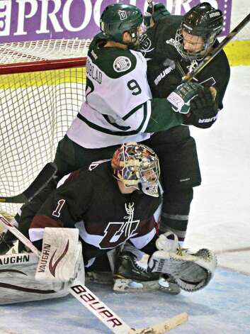 Dartmouth's #Matt Lindblad crowds Union's  goalie #1 Troy Grosenick and #12 Kyle Bodie during Friday's game at Messa Rink in Schenectady Feb. 1, 2013.  (John Carl D'Annibale / Times Union) Photo: John Carl D'Annibale / 00020976A