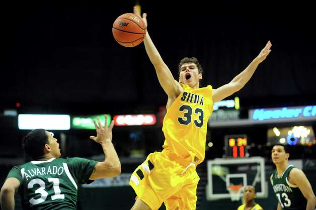 Siena's Rob Poole (33), center, loses the ball after a foul from Manhattan's Michael Alvarado (31), left, during their basketball game on Friday, Feb. 1, 2013, at Times Union Center in Albany, N.Y. Siena wins 66-63. (Cindy Schultz / Times Union) Photo: Cindy Schultz / 00020987A