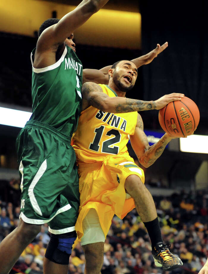 Siena's Rakeem Brookins (12), right, goes to the hoop as Manhattan's Rhamel Brown (5) defends during their basketball game on Friday, Feb. 1, 2013, at Times Union Center in Albany, N.Y. (Cindy Schultz / Times Union) Photo: Cindy Schultz / 00020987A