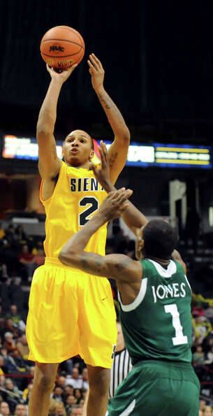 Siena's Trenity Burdine (2), left, shoots and hits a 3-point basket as Manhattan's CJ Jones (1) defe