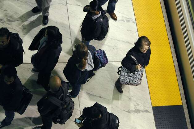 A woman waits for BART at the Embarcadero station on February 1st, 2013 in San Francisco, Calif. BART is planning on spending $650 million-plus to expand San Francisco's Embarcadero and Montgomery Street station platforms, knocking out the walls behind the trains and drilling new tunnels behind with access to the street. Embarcadero is very crowed during its peak time. Photo: Jessica Olthof, The Chronicle