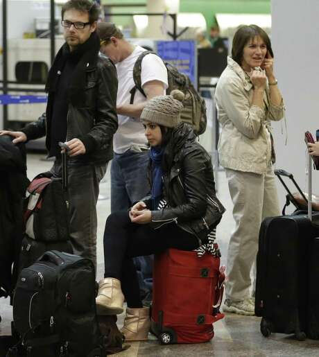 Passengers wait for flights in Salt Lake City. Some airlines drastically changed baggage fees last year. Photo: Rick Bowmer, STF / AP