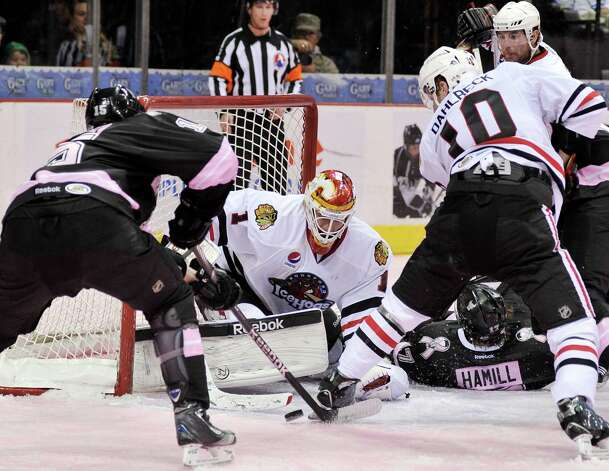 Rockford IceHogs goaltender Henrik Karlsson (1) makes a save on San Antonio Rampage's Eric Selleck, left, as Rockford's Klas Dahlbeck (10) defends the net during the second period of an AHL hockey game, Friday, Feb. 1, 2013, in San Antonio. (Darren Abate/pressphotointl.com) Photo: Darren Abate, For The Express-News / Darren Abate/pressphotointl.com