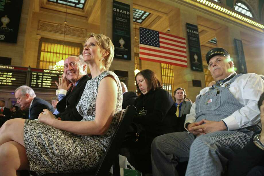 New York poet Billy Collins, second from left, Broadway star Cynthia Nixon, third from left, and retired Amtrak conductor Tom Savio, right, are among invited guests attending the Grand Central Terminal centennial celebration on Friday, Feb. 1, 2013 in New York. Grand Central, once in danger of being demolished, is celebrating its 100th birthday with speeches, a brass band and a rollback to 1913 prices when a slice of cheesecake might go for 19 cents. The majestic Beaux Arts building, known as Grand Central station although it is technically a terminal, is one of the world's most popular tourist destinations. Photo: Bebeto Matthews, AP / AP
