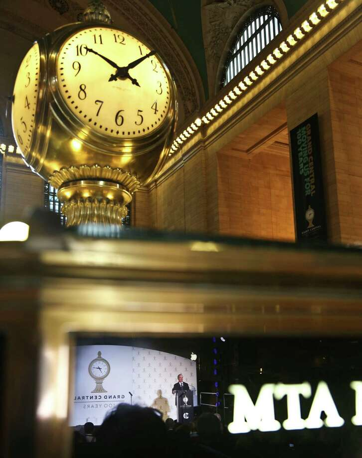A reflection of Mayor Michael Bloomberg is caught in the window of the booth hosting the Grand Central Terminal clock, a four convex face made of opal, as he speaks during its 100th birthday celebration on Friday, Feb. 1, 2013 in New York.  Mayor Bloomberg remembered former Mayor Ed Koch,  who died early this morning at 88, recalling his role in helping to restore the terminal. Photo: Bebeto Matthews, AP / AP