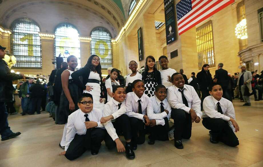 NEW YORK, NY - FEBRUARY 01:  Students from the William Lloyd Harrison school in the Bronx pose in Grand Central Terminal before performing during centennial celebrations on the day the famed Manhattan transit hub turns 100 years old on February 1, 2013 in New York City. The terminal opened in 1913 and is the world's largest terminal covering 49 acres with 33 miles of track. Each day 700,000 people pass through the terminal where Metro-Noth Railroad operates 700 trains per day. Photo: Mario Tama, Getty Images / 2013 Getty Images