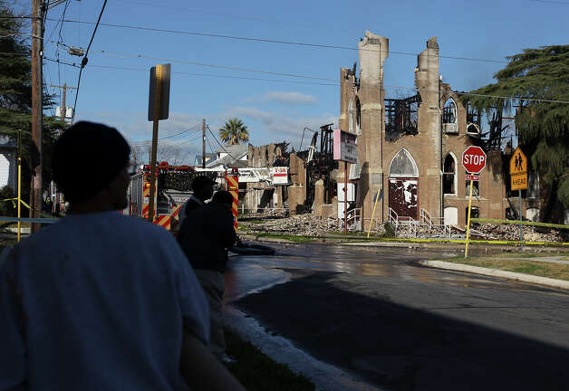Area residents view the remnants of the Childress Memorial Church of God in Christ after a fire destroyed the historic building on Saturday, Feb. 2, 2013. A two-alarm fire at the church after midnight had multiple fire crews on the scene attempting to extinguish flames topping the building. Firefighters and arson investigators were on the scene shortly after sunrise to assess the cause. Photo: Kin Man Hui, San Antonio Express-News / © 2012 San Antonio Express-News