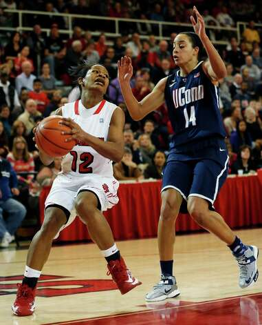 St. John's guard Briana Brown (12) looks to pass around Connecticut guard Bria Hartley (14) during the second half of an NCAA college basketball game, Saturday, Feb. 2, 2013, at St. John's University in New York. Connecticut defeated St. John's 71-65. (AP Photo/John Minchillo) Photo: John Minchillo, Associated Press / FR170537 AP