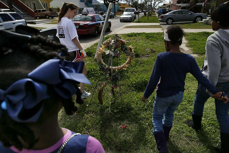 Makayla Barton, a volunteer from Tulane University (top center), walks up to a memorial to victims of Hurricane Katrina with (l-r) Chyana Hurst, 9, Shamiya Thomas, 9, and Shaniya Thomas, 12, who live in the Ninth Ward of New Orleans, La., on Saturday, February 2, 2013. Hurst and the Thomas's lost several family members in the devastation that followed Katrina. Photo: Carlos Avila Gonzalez, The Chronicle