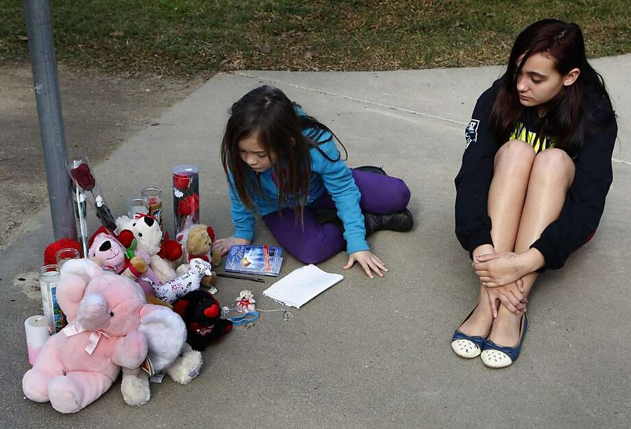 Anayah Hyde (left) and Anastasia Keola visit a memorial for the slaying victim. Photo: Paul Chinn, The Chronicle