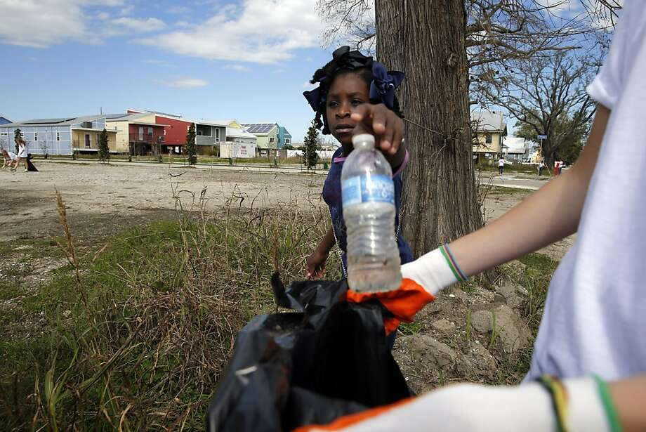 Chyana Hurst, 9, throws away a bottle as she helps Tulane University volunteers clean up in the Ninth Ward of New Orleans, La., on Saturday, February 2, 2013, as part of the Make It Right day of volunteering. Photo: Carlos Avila Gonzalez, The Chronicle