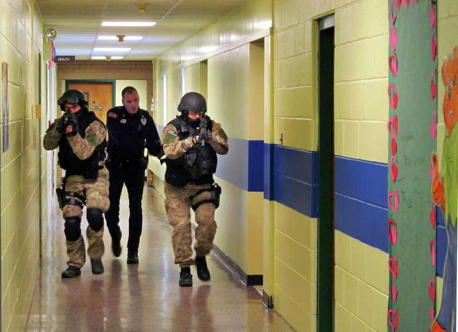 FILE - In this file photo of Jan. 28, 2013, members of the Washington County Sheriff's Office and the Hudson Falls Police Department use unleaded guns to take part in an emergency drill as they walk through a corridor inside the Hudson Falls Primary School in Hudson Falls, N.Y. School security has come under more scrutiny in the wake of the Sandy Hook Elementary School massacre in Newtown, Conn., that killed 26 people in December. (AP Photo/The Post-Star, Omar Ricardo Aquije, File) Photo: Omar Ricardo Aquije, ASSOCIATED PRESS / A2013