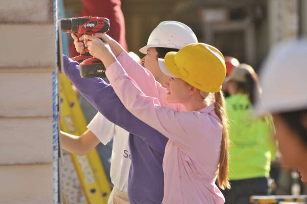 Caroline Miller uses a drill while building a Habitat for Humanity home Saturday morning. She was one of over 250 volunteers working on 9 Habitat homes in the Morning Star Terrace project. Photo: Robin Jerstad, For The Express-News