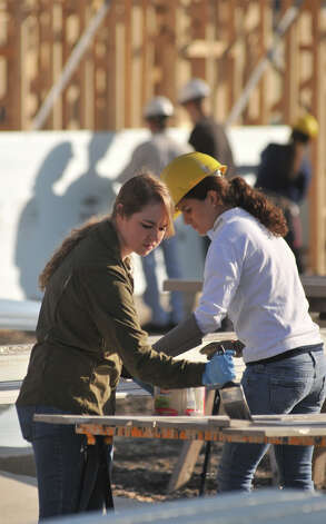 Rachel Palmer and Elena Camargo paint during a Habitat for Humaniity build Saturday at Morning Star Terrace. Over 250 people volunteered to build 9 houses. Photo: Robin Jerstad, For The Express-News