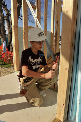 Joshua Milford-Rosales hammers on one of 9 Habitat for Humanity homes being build in the Morning Star Terrace project Saturday. Photo: Robin Jerstad, For The Express-News