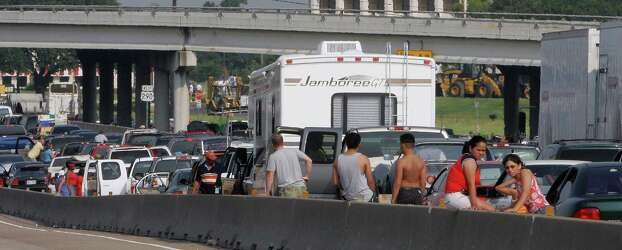 ** FILE ** Storm evacuees stand on the side of Highway 290 that became a parking lot as people attempt to flee the approach of Hurricane Rita in Houston on Thursday, Sept. 22, 2005. State and local officials have taken a beating for waiting until millions of Hurricane Rita evacuees had been trapped in gridlock for more than 24 hours before they opened Houston's major highways to one-way outbound traffic. But the Texas Department of Transportation says it wasn't easy to convert 487 miles of highway, including two interstates, to one-way traffic. (AP Photo/Ron Heflin, File) Photo: RON HEFLIN, STF / AP