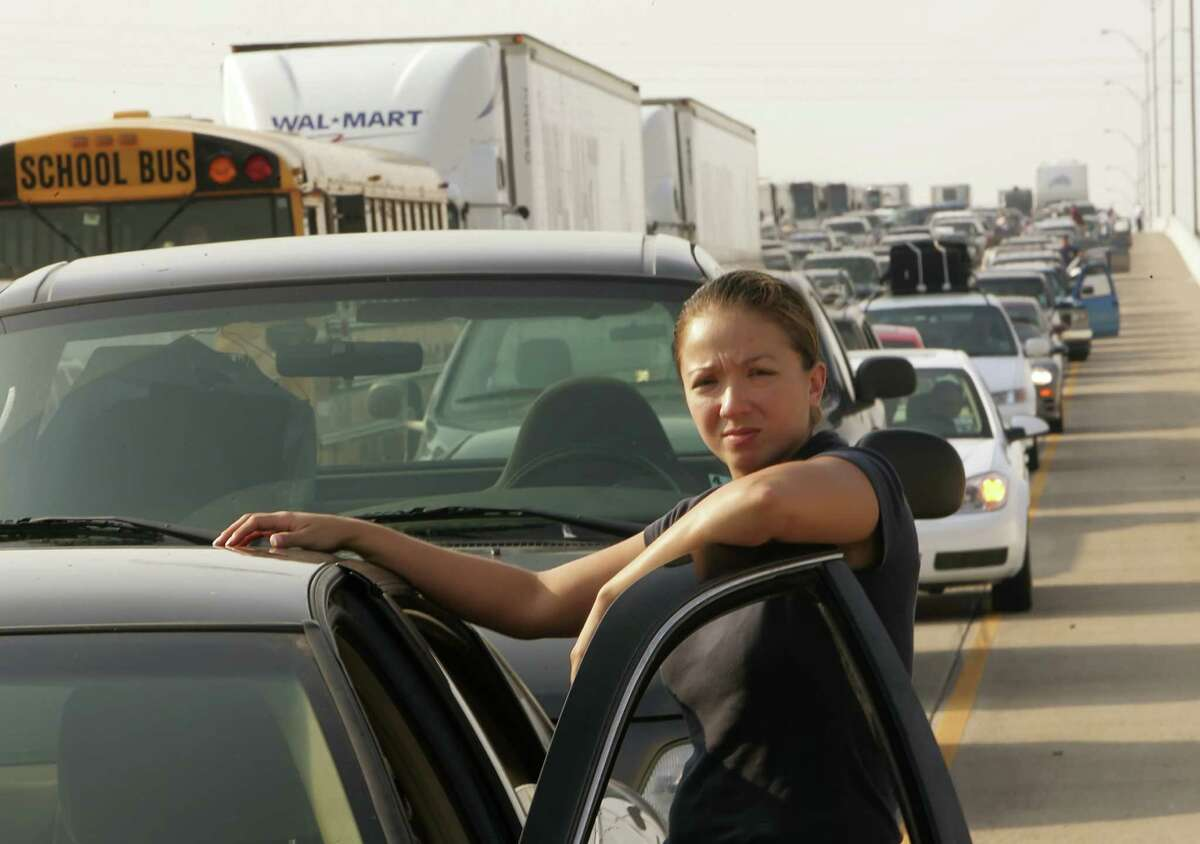 Martha Velazquez stands on the road during stalled traffic while she tries to evacuate in advance of Hurricane Rita in east Houston September 22, 2005. Hurricane Rita weakened slightly to 165 miles per hour but still remained a dangerous Category 5 storm, according to the U.S. National Hurricane Center on Thursday. REUTERS/Rick Wilking