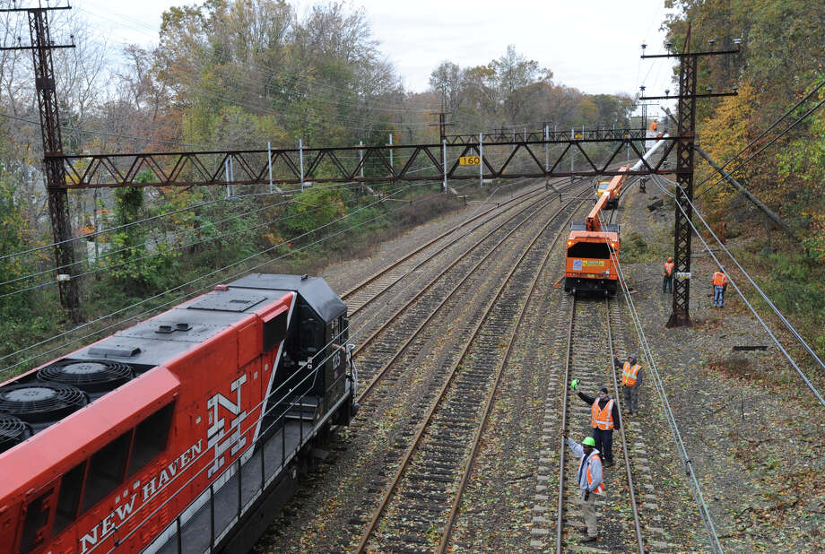A New Haven Line Metro-North train heads north past a clean-up crew that was attempting to clear a downed tree that was resting on the electric lines by the railroad tracks near the West Street overpass in Mamaroneck, N.Y. during the aftermath of Hurricane Sandy. Metro-North is now planning to trim trees in Greenwich and Stamford that seeks to avoid a repeat of last August's power outage, when a tree fell on a main transmission line, knocking out power to 99 percent of Greenwich. Photo: Bob Luckey / Greenwich Time