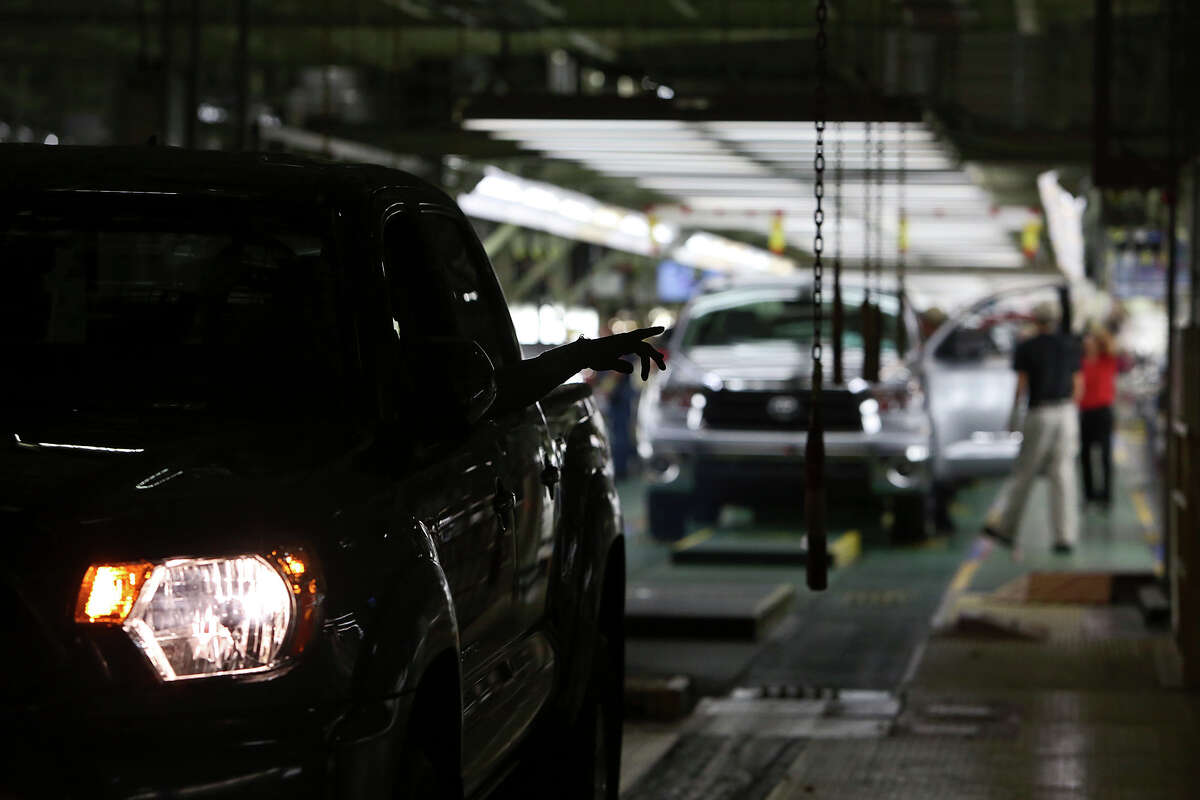 Workers keep trucks moving off the final inspection line at a rate of one in just over a minute at the Toyota plant.