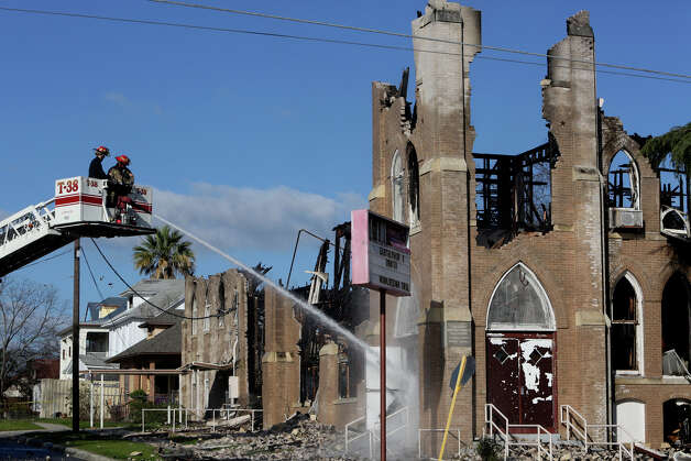 Firefighters continue to put out hot spots Saturday in the wake of the overnight blaze that reduced the Childress Memorial Church of God in Christ to a charred and crumbling shell. Photo: Lisa Krantz, San Antonio Express-News / © 2012 San Antonio Express-News