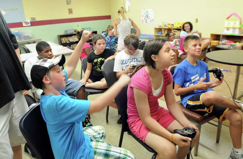 Jakob Majkut, 11, left, cheers as Jessica Cunningham, 13, center, and Jordan West, 12, right, play a World Cup soccer video game on Wednesday, Aug. 11, 2010, at the Cohoes Community Center in Cohoes, N.Y. The center received $3,500 from the Times Union Hope Fund to benefit their summer camp, Operation Helping Hand. (Cindy Schultz / Times Union) Photo: Cindy Schultz / 00009814A