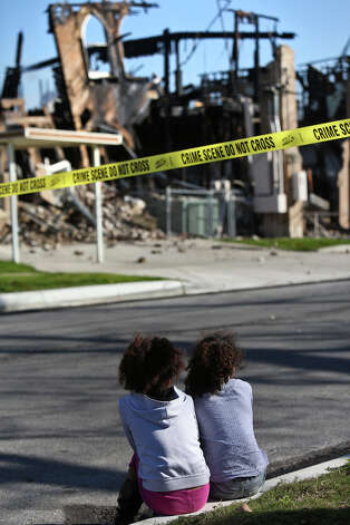 "Twins Jayla Compian, left, and Janae, 7, watch as firefighters continue to work at the scene of multi-alarm fire overnight at Childress Memorial Church Of God In Christ in San Antonio on Saturday, Feb. 2, 2013. Their mother, Louise Tovar, was raised in the church and they have attended it too. ""I haven't been in a very, very long time and my intentions were to come tomorrow,"" Tovar said. Photo: Lisa Krantz, San Antonio Express-News / © 2012 San Antonio Express-News"
