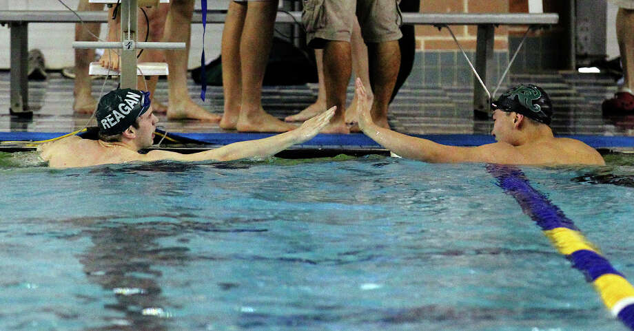 Reagan's Andrew Skowroneck (left) and teammate Joseph Tak give each other a high-five after the 100-yard butterfly at the District 26-5A swim meet at Josh Davis Natatorium on Saturday, Feb. 2, 2013. Skowroneck finished first and bested his district record time from last year with a 50.66 finish. Tak finished in second. Photo: Kin Man Hui, San Antonio Express-News / © 2012 San Antonio Express-News