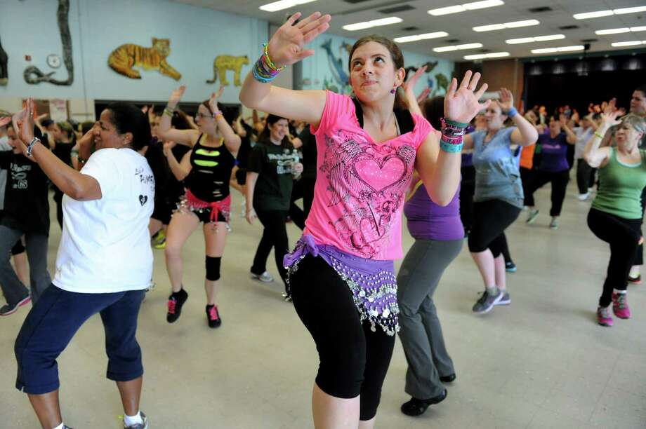 Self-proclaimed Zumbaholic, Jennifer Walker of Colonie, center, participates in a Zumbathon fundraiser in honor of Deanna Rivers and Chris Stewart on Saturday, Feb. 2, 2013, at Orenda Elementary School in Clifton Park, N.Y. Proceeds from ticket sales, raffles , baked goods and vendor sales will benefit the scholarship funds of these Shenendehowa athletes who died in a car crash. (Cindy Schultz / Times Union) Photo: Cindy Schultz / 10021020A