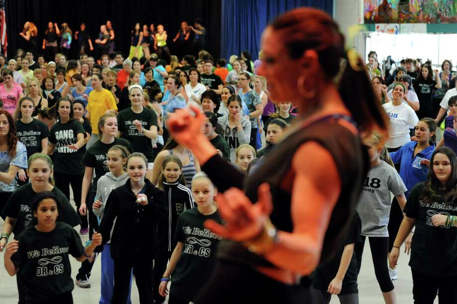 Zumba instructor Rene Scavio, center, leads a Zumbathon fundraiser in honor of Deanna Rivers and Chris Stewart on Saturday, Feb. 2, 2013, at Orenda Elementary School in Clifton Park, N.Y. Proceeds from ticket sales, raffles , baked goods and vendor sales will benefit the scholarship funds of these Shenendehowa athletes who died in a car crash. (Cindy Schultz / Times Union) Photo: Cindy Schultz / 10021020A