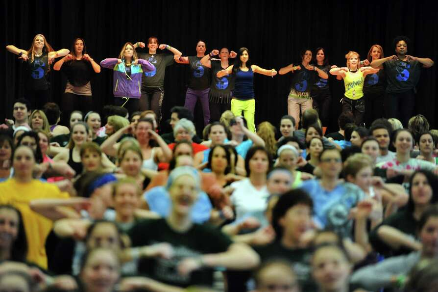 Zumba instructors dance on a second stage during a Zumbathon fundraiser in honor of Deanna Rivers an