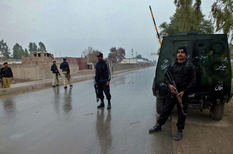 Pakistani policemen cordon the area near a military checkpoint after an attack Saturday by militants about 150 miles south of Peshawar. Photo: Karim Ullah, AFP/Getty Images / AFP