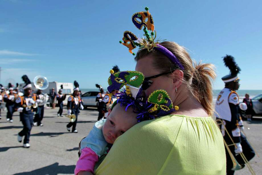 Tiffany Diettel right, hold her one-year-old daughter Kaylee Diettel during the Mystic Krewe of Aquarius 25th annual Mardi Gras Kick off Parade along Seawall Blvd. Saturday, Feb. 2, 2013, in Galveston. Photo: James Nielsen, Chronicle / © Houston Chronicle 2013