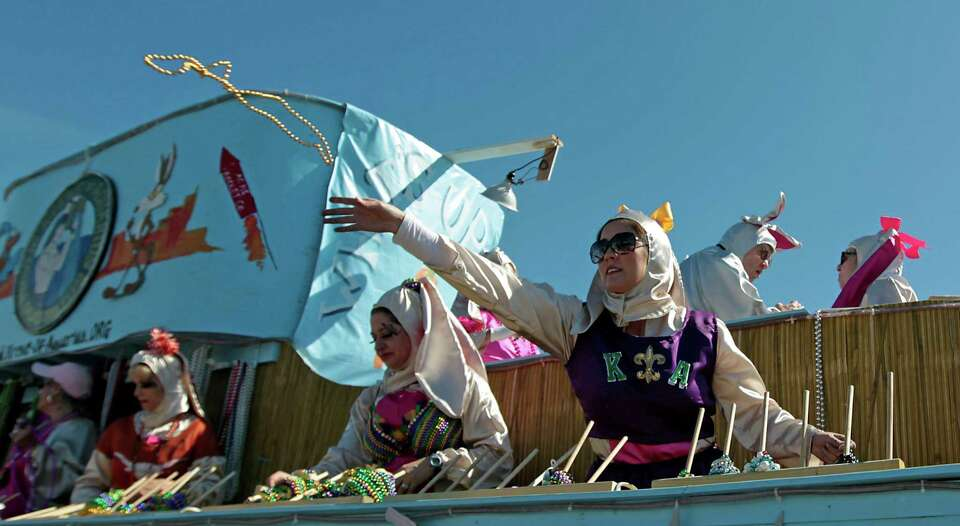 People aboard a float toss beads during the Mystic Krewe of Aquarius 25th annual Mardi Gras Kick off
