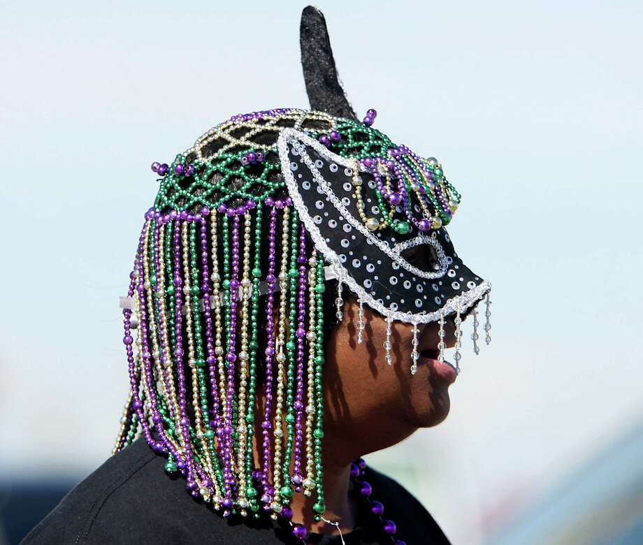 Maccine Lewis watches the Mystic Krewe of Aquarius 25th annual Mardi Gras Kick off Parade along Seawall Blvd. Saturday, Feb. 2, 2013, in Galveston. Photo: James Nielsen, Chronicle / © Houston Chronicle 2013